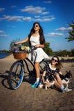 2 красивых девушки с велосипедом и французскими бульдогами Стоковые Фотографии RF