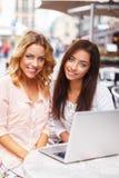 2 красивых девушки с компьтер-книжкой Стоковое Фото