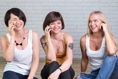 3 красивых девушки с мобильным телефоном Стоковая Фотография
