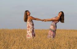 2 красивых девушки танцуют в поле овса Стоковое Изображение