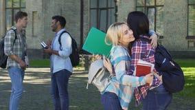 2 красивых женских друз обнимая около кампуса, долгожданного назначения акции видеоматериалы
