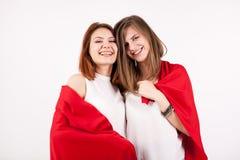 2 красивых женских друз покрывая их собственная личность с красным одеялом Стоковое фото RF