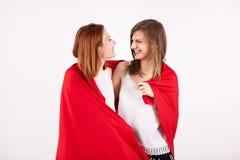 2 красивых женских друз покрывая их собственная личность с красным одеялом Стоковая Фотография