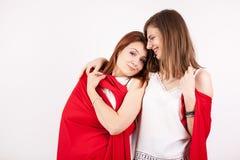 2 красивых женских друз покрывая их собственная личность с красным одеялом Стоковое Фото