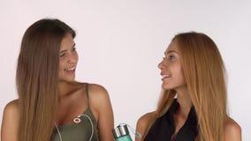 2 красивых женских друз усмехаясь к камере, представляя в одежде разминки видеоматериал