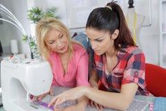 2 красивых женских портноя работая в магазине портноя Стоковое фото RF