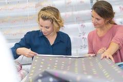 2 красивых женщины выбирая ткань на магазине ткани Стоковое фото RF