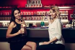 2 красивых женщины выпивая коктеиль в ночном клубе и имея Стоковые Изображения