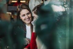 2 красивых женщины выпивая кофе и беседуя в кафе Стоковые Изображения RF