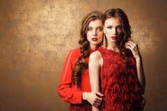 2 красивых женщины в красных платьях Совершенные состав и стиль причёсок Стоковое Изображение RF