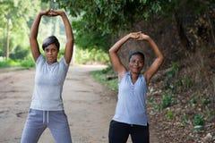 2 красивых женщины делая протягивающ тренировку в парке стоковое изображение