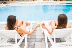 2 красивых женщины имея коктеили совместно бассейном взрослые молодые Стоковые Фото
