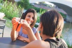 2 красивых женщины имея коктеиль внешний на заходе солнца Стоковая Фотография RF