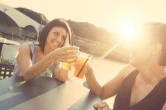 2 красивых женщины имея коктеиль внешний на заходе солнца Стоковая Фотография