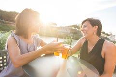 2 красивых женщины имея коктеиль внешний на заходе солнца Стоковые Фотографии RF
