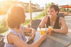 2 красивых женщины имея коктеиль внешний на заходе солнца Стоковое Изображение