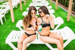 2 красивых женщины ослабляя в бассейне с коктеилями Лето Стоковые Изображения
