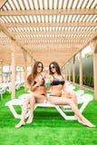 2 красивых женщины ослабляя в бассейне с коктеилями Лето Стоковое Изображение RF