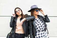 2 красивых женщины представляя в городке модно и стильные стоковое фото rf