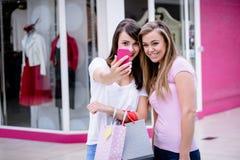 2 красивых женщины принимая selfie в торговом центре Стоковая Фотография