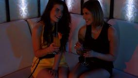 2 красивых женщины сидя на софе и имея коктеиль сток-видео