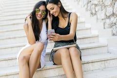 2 красивых женщины смотря телефон Стоковое Изображение