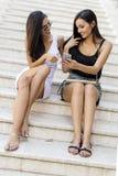 2 красивых женщины смотря телефон Стоковые Фотографии RF