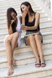 2 красивых женщины смотря телефон Стоковые Изображения RF