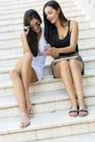 2 красивых женщины смотря телефон Стоковое Изображение RF