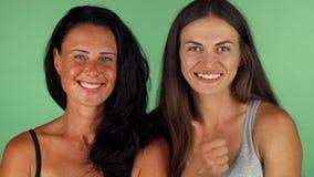 2 красивых женщины усмехаясь показывающ большие пальцы руки вверх на chromakey акции видеоматериалы