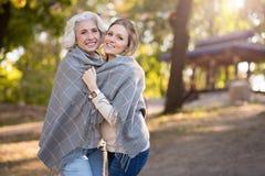 2 красивых жизнерадостных женщины обнимая под шотландкой Стоковое фото RF