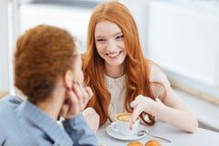 2 красивых жизнерадостных молодой женщины говоря в кафе совместно Стоковые Изображения RF