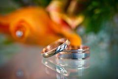 2 красивых золотых кольца на запачканной оранжевой предпосылке Стоковые Изображения