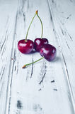 3 красивых красных вишни на белом деревянном столе Стоковые Изображения RF