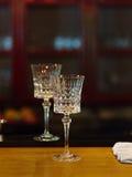 2 красивых кристаллических пустых рюмки на latticed предпосылке Прозрачные стекла Стоковое Изображение