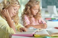 2 красивых маленькой девочки на классе прочитали книгу и сочинительство на не Стоковые Изображения RF