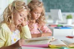 2 красивых маленькой девочки на классе прочитали книгу и сочинительство на не Стоковое фото RF