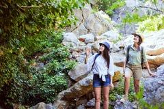2 красивых маленькой девочки путешествуют в горах и наслаждаются взглядом ландшафта зеленых деревьев Стоковое Изображение RF