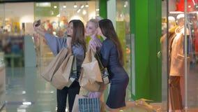 3 красивых маленькой девочки держа хозяйственные сумки, фотографирующ, делая selfie Девушки смеясь над и усмехаясь на видеоматериал