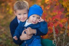 2 красивых милых брать сидя на тыкве в лесе осени самостоятельно Стоковые Фотографии RF