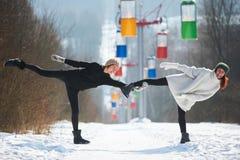 2 красивых молодой женщины делая йогу outdoors в парке зимы Стоковые Изображения RF