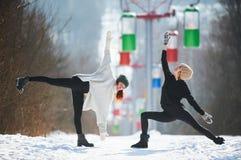 2 красивых молодой женщины делая йогу outdoors в парке зимы Стоковое Изображение
