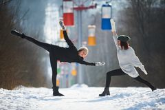 2 красивых молодой женщины делая йогу outdoors в парке зимы Стоковая Фотография