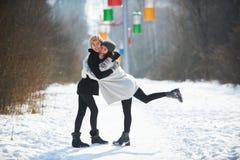 2 красивых молодой женщины обнимая и усмехаясь outdoors в парке зимы Стоковое Изображение RF