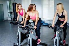 3 красивых молодой женщины разрабатывая на велосипедах на спортзале Стоковые Фотографии RF