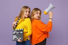2 красивых молодых белокурых девушки сестер близнецов держат классическое черное clapperboard создания фильма, клекот на изолиров стоковое изображение