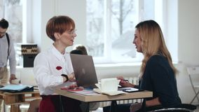 2 красивых молодых кавказских женщины менеджера говоря положение на современной ультрамодной таблице офиса Здоровое рабочее место акции видеоматериалы