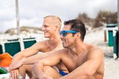 2 красивых молодого человека беседуя на пляже стоковое фото rf
