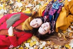 2 красивых молодой женщины лежа на желтых листьях Стоковые Изображения RF