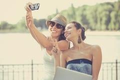 2 красивых молодой женщины делая смеяться над selfie Стоковая Фотография RF